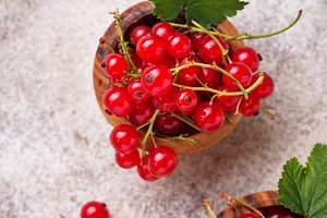 Ripe red currant berries in wooden