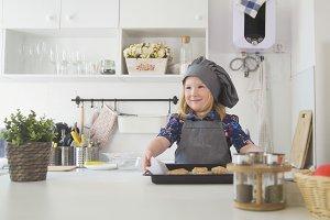 Preschool girl baker holding a