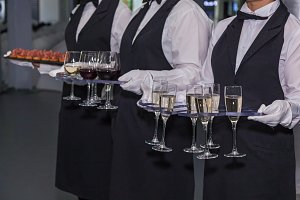 The waiter holds glasses of wine