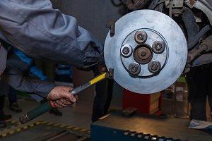 The man is repairing the disc brake