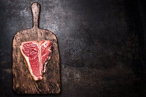 Raw T-bone steak on aged wooden