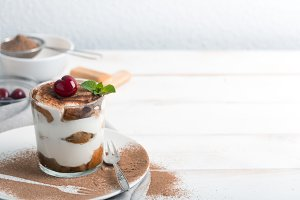 Tiramisu and cherry in a glass cup