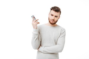 Annoyed young man holding smartphone