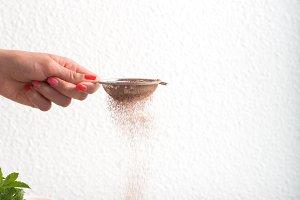 Woman powders cocoa powder on