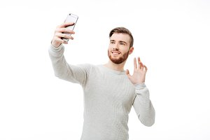 Cheerful handsome man taking selfie