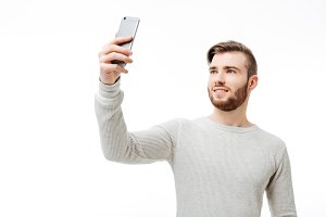 Happy casual man taking selfie over
