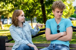 A guy with a girl on a park bench