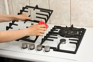 hands cleaning gas cooker