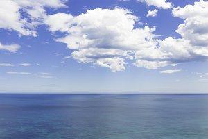 blue cloudy sky over the blue sea