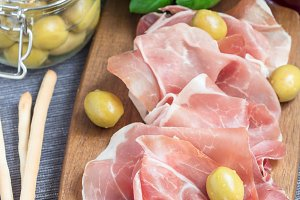 Prosciutto ham on wooden board with