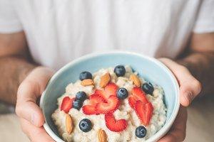Oatmeal porridge bowl in hands. Vega