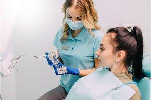 woman dentist advises woman patient