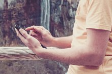 Man using a tablet. Nature,waterfall