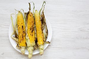 Grilled sweet corn on a white round