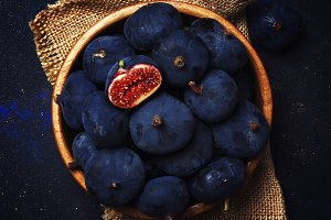 Ripe blue fresh figs in a wooden bow