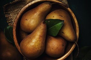 Ripe brown pears in a wooden bowl, d