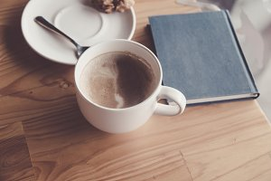 Coffee cup on wood table with blue b