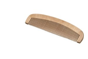 closeup brown wooden comb on a white