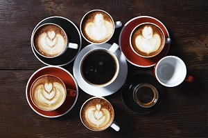 Many cups of coffee on wooden table,