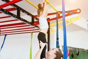 Little girl hanging on the crossbar,