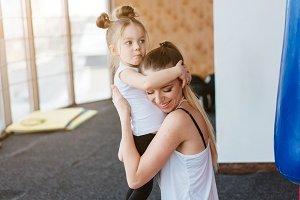 Mom hugs her little daughter