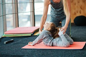 A little girl repeats exercises for