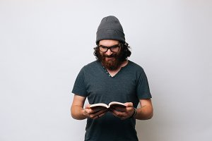 Young bearded hipster man reading.