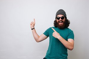 bearded hipster man pointing up