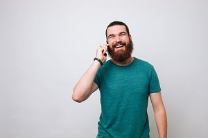 man with beard talking on phone