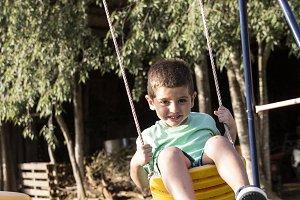 Cute little blond boy swinging