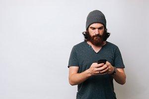 Serios young bearded man looking at