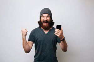 Cheerful young bearded man wearing g