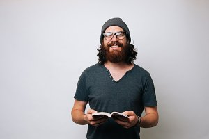 man with eyeglasses holding a book