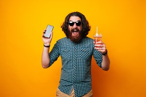 man holding a phone and juice drink