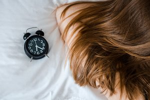 Woman sleeping with alarm clock