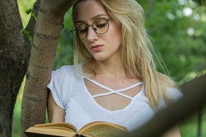 Young woman student reading a book