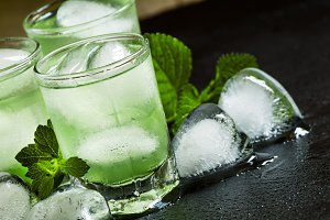 Green cold drink with ice in a heart