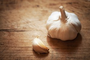 raw garlic on a wooden plank