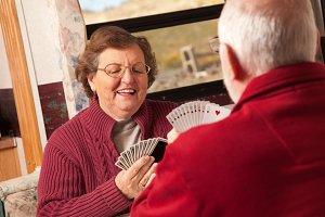 Happy Senior Adult Couple Playing Ca