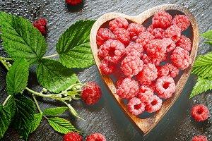 Fresh raspberries with leaves in a b