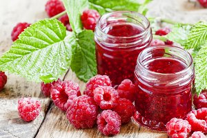 Two jars of raspberry jam, fresh ber