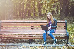Hipster girl use laptop in a park