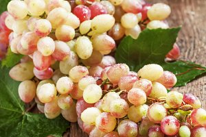 Pink grapes with green leaves on old