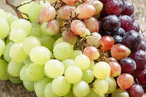 Green, pink and purple grapes on old