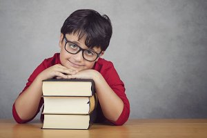 boy leaning on books on a table
