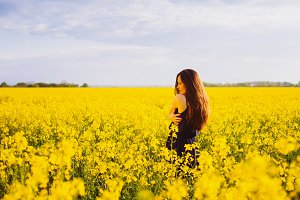 Girl hugs herself on rapeseed meadow
