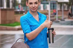 Girl with mug of thermos with coffee