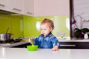 Small baby boy feeding himself