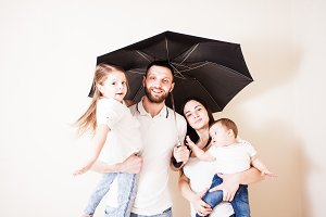 Young father holding umbrella upon