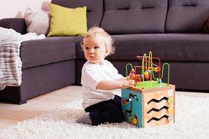 Baby boy playing on soft carpet